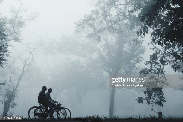 side view of man riding bicycle against sky - smog stock pictures, royalty-free photos & images