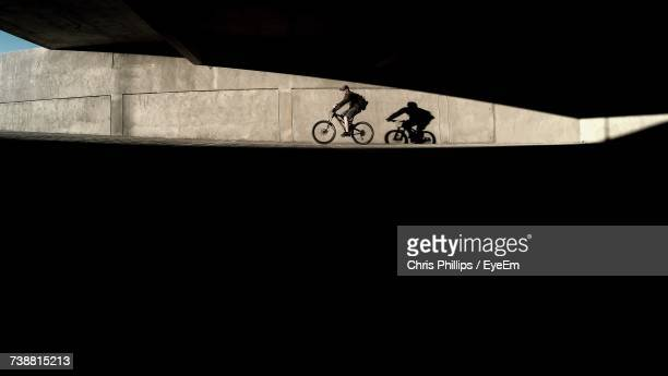 Side View Of Man Riding Bicycle Below Bridge On Sunny Day