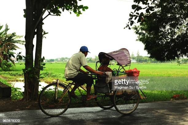 Side View Of Man Riding Cart On Road Against Sky