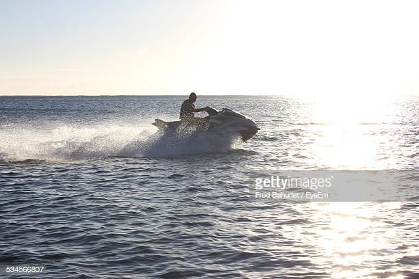 Side View Of Man Riding Jet Ski On Sunny Day