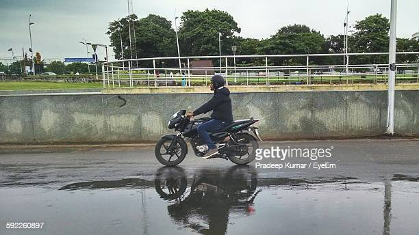 Side View Of Man Riding Motorcycle On Wet Street Against Park