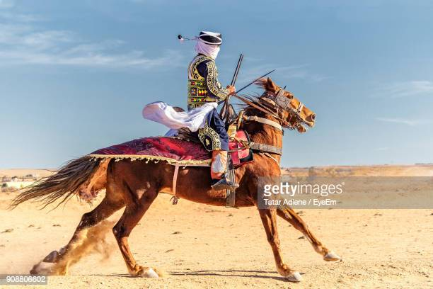 side view of man riding on sand at field against sky - algerie photos et images de collection