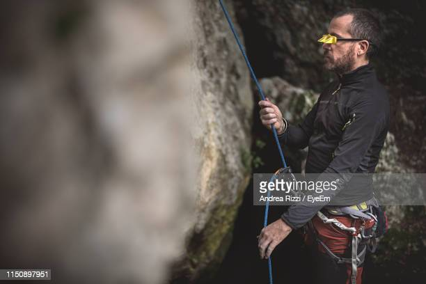 side view of man rock climbing - andrea rizzi stockfoto's en -beelden