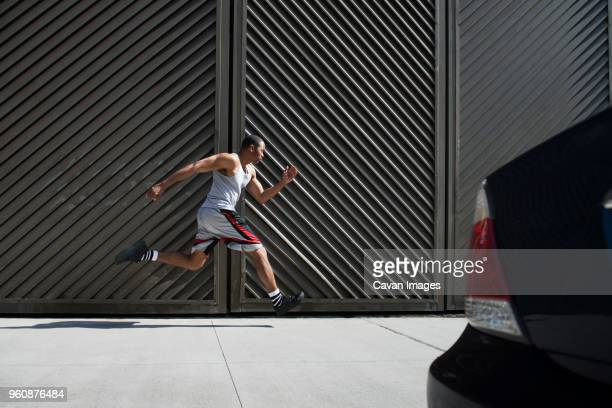 Side view of man running against wall