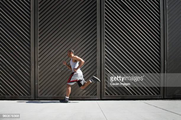 Side view of man running on floor against metal wall