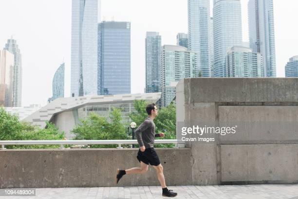 side view of man running on footbridge against modern buildings in city - homens de idade mediana - fotografias e filmes do acervo