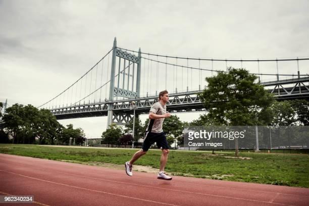 side view of man running on sports track against triborough bridge - east harlem - fotografias e filmes do acervo