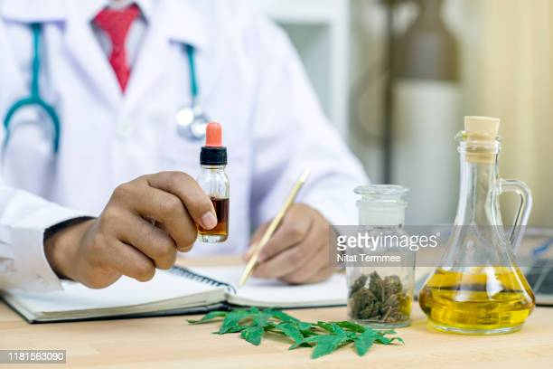 side view of man scientist in laboratory testing oil extracted from a marijuana plant. - marijuana leaf stock pictures, royalty-free photos & images
