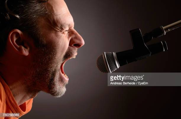 side view of man shouting in microphone against gray background - crier photos et images de collection