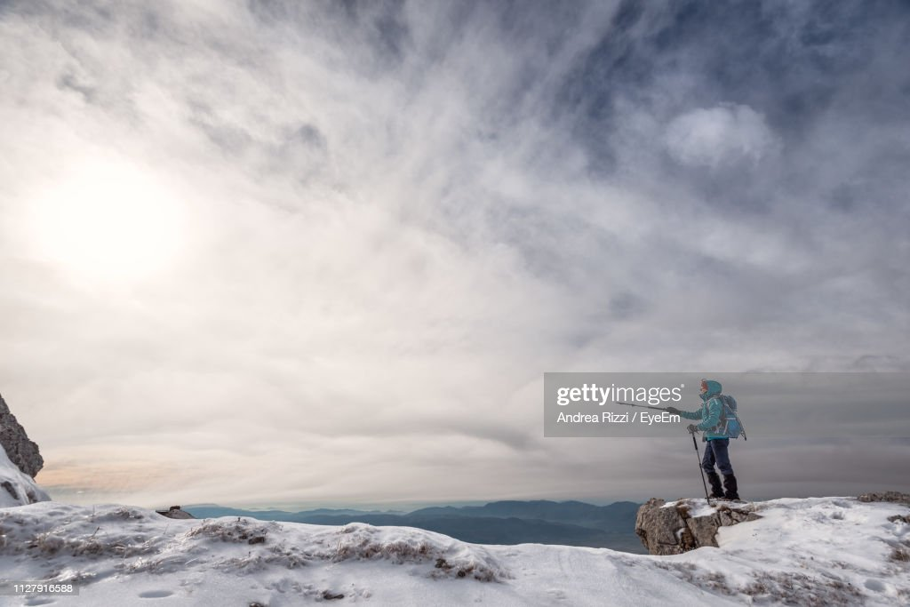 Side View Of Man Showing With Hiking Pole While Standing On Snow Against Sky : Foto stock