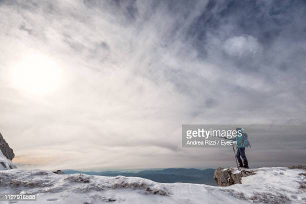 Side View Of Man Showing With Hiking Pole While Standing On Snow Against Sky