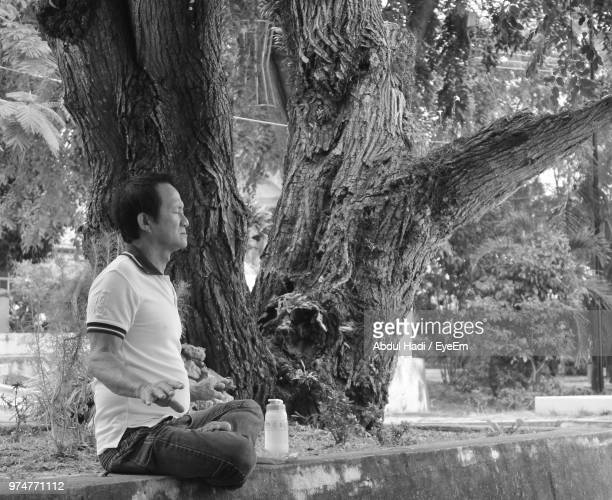 Side View Of Man Sitting By Tree Trunk