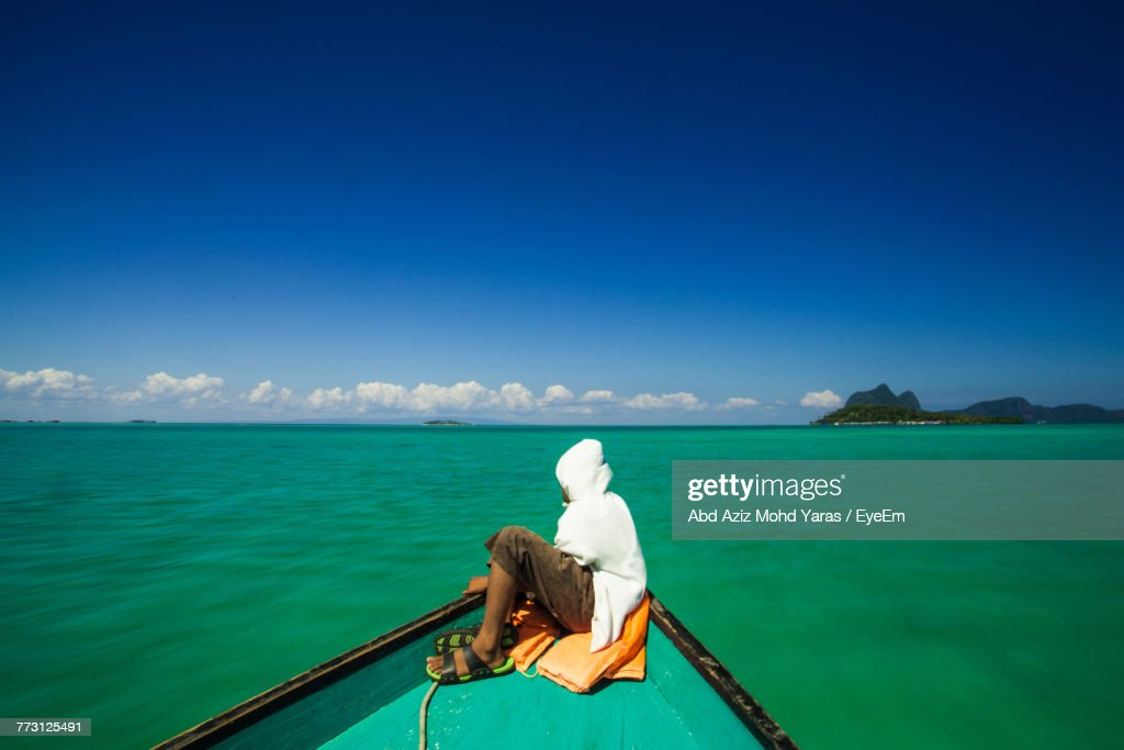 Side View Of Man Sitting In Boat On Sea Against Blue Sky : Photo