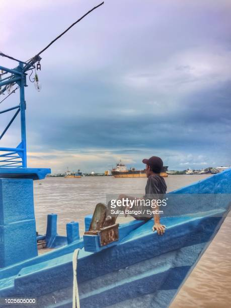 side view of man sitting on blue boat in sea against cloudy sky - west kalimantan stock pictures, royalty-free photos & images