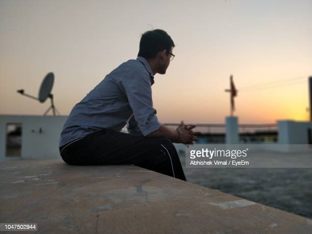 Side View Of Man Sitting On Building Terrace Against Sky During Sunset