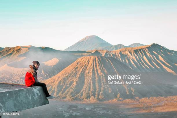 Side View Of Man Sitting On Built Structure Against Mountains