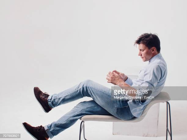 Side View Of Man Sitting On Chair Against White Background