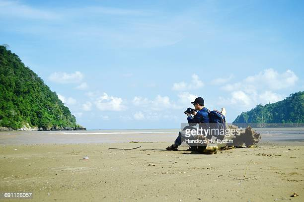 Side View Of Man Sitting On Driftwood While Photographing At Beach Against Sky