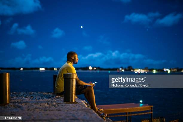 side view of man sitting on pier by sea at night - kenya stock pictures, royalty-free photos & images