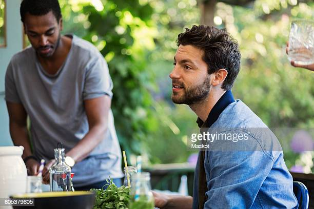 Side view of man sitting on porch at log cabin during summer party