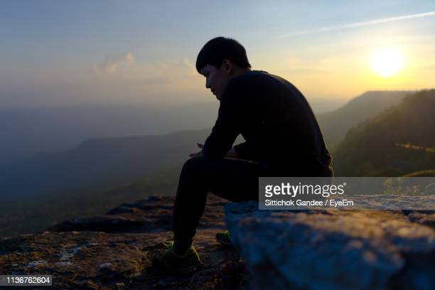 Side View Of Man Sitting On Rock Against Sky During Sunset