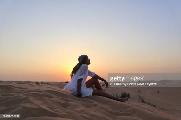 side view of man sitting on sand at desert against clear sky during sunset - dubai strand stock-fotos und bilder