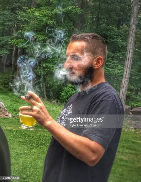 Side View Of Man Smoking Cigar While Holding Drink