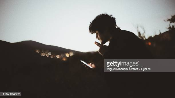 side view of man smoking cigarette against sky - 25 29歳 ストックフォトと画像