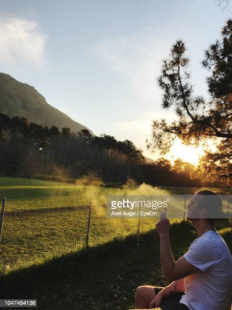 Side View Of Man Smoking On Field During Sunset