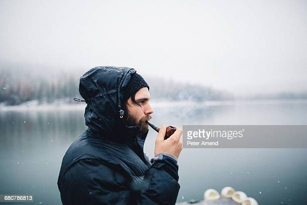 Side view of man smoking pipe by lake, Bass Lake, California, USA