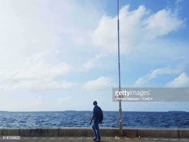 Side View Of Man Standing Against Sea And Cloudy Sky