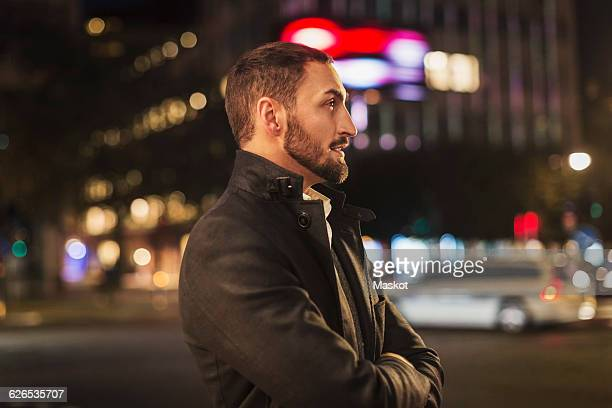 Side view of man standing arms crossed on city street at night