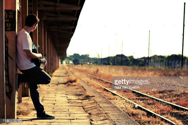 side view of man standing at old railroad station - assis ストックフォトと画像
