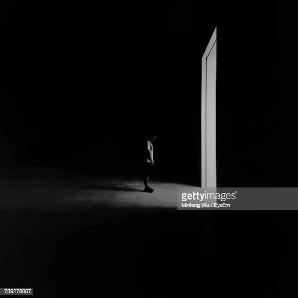 side view of man standing by doorway in darkroom at night - doorway stock pictures, royalty-free photos & images