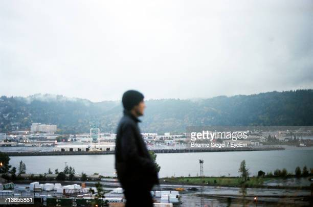 Side View Of Man Standing In City Against Clear Sky