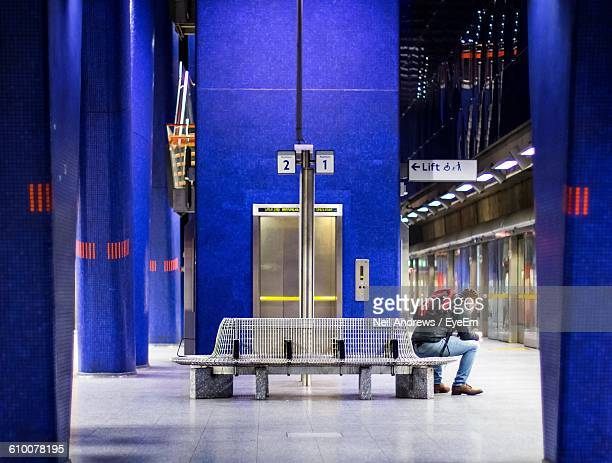 Side View Of Man Standing On Bench At Subway Platform