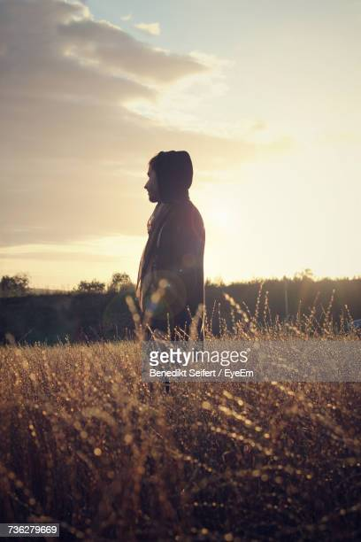 Side View Of Man Standing On Field Against Sky During Sunset