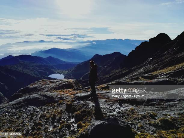 side view of man standing on mountains against sky - wally yegiora stock photos and pictures