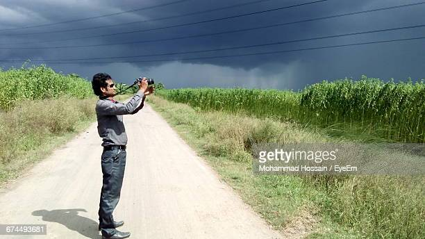 Side View Of Man Standing On Road While Photographing Against Cloudy Sky Using Camera
