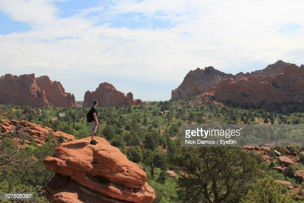 side view of man standing on rock against forest - garden of the gods stock photos and pictures