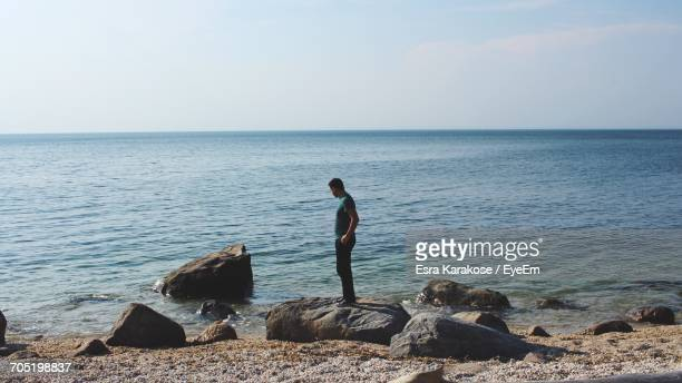 Side View Of Man Standing On Rock By Sea Against Sky