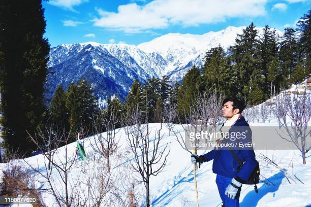 Side View Of Man Standing On Snowcapped Mountain Against Sky