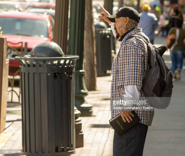 side view of man standing on street, preaching - steven cottingham stock-fotos und bilder
