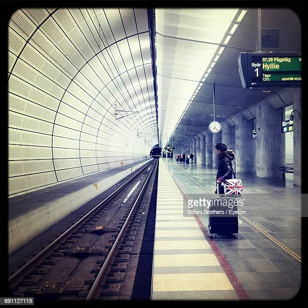 side view of man standing with luggage at illuminated subway station - metrostation stockfoto's en -beelden