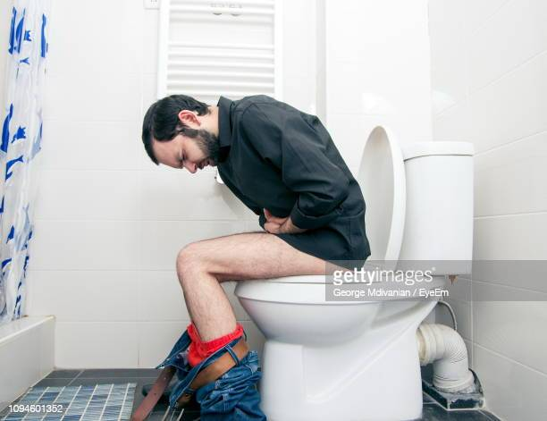side view of man suffering from stomachache sitting on toilet seat - men taking a dump stock pictures, royalty-free photos & images