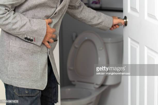 Side View Of Man Suffering From Stomachache Sitting On Toilet Seat