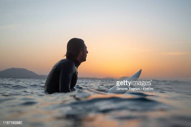 side view of man surfing in sea against sky during sunset - surf ストックフォトと画像