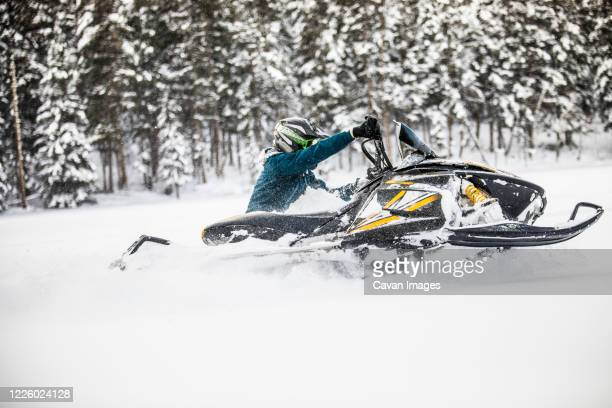 side view of man turning snowmobile in deep powder. - motorsport stock pictures, royalty-free photos & images