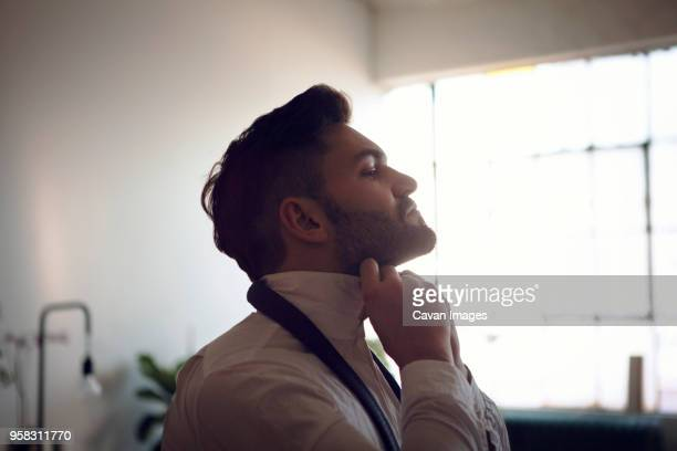 side view of man tying necktie - tie stock pictures, royalty-free photos & images