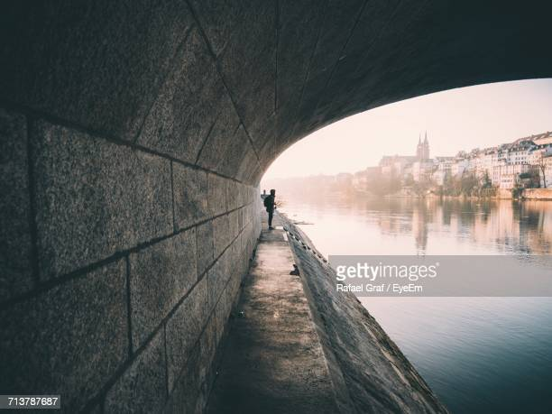 side view of man under bridge over water - basel switzerland stock pictures, royalty-free photos & images